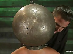 Adrianna Luna has her legs held apart by a support and her hands are encased by metal balls. Her head is encased by a metal ball as well and pumps on her nipples. She receives a sex tool on her cunt and receives the okay to cum. Then she's tied to a table and having clamps put on her cunt and tits. Freaky!